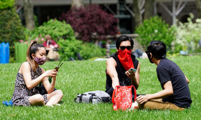 Three people wear protective masks while sitting on the lawn in Bryant Park in New York City, N.Y., on May 22, 2020. (Cindy Ord/Getty Images)
