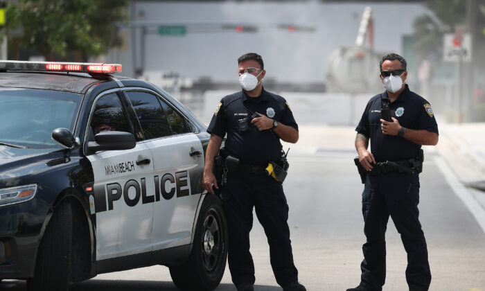 Miami Beach police officers wear protective masks as Florida Gov. Ron DeSantis along with other officials and politicians speak during a press conference at the Miami Beach Convention Center in Miami Beach, Fla. on April 08, 2020. (Joe Raedle/Getty Images)