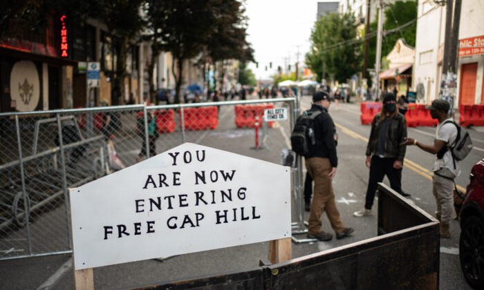 "A sign is seen on a barrier at an entrance to the so-called ""Capitol Hill Autonomous Zone,"" in Seattle, Wash., on June 10, 2020. (David Ryder/Getty Images)"