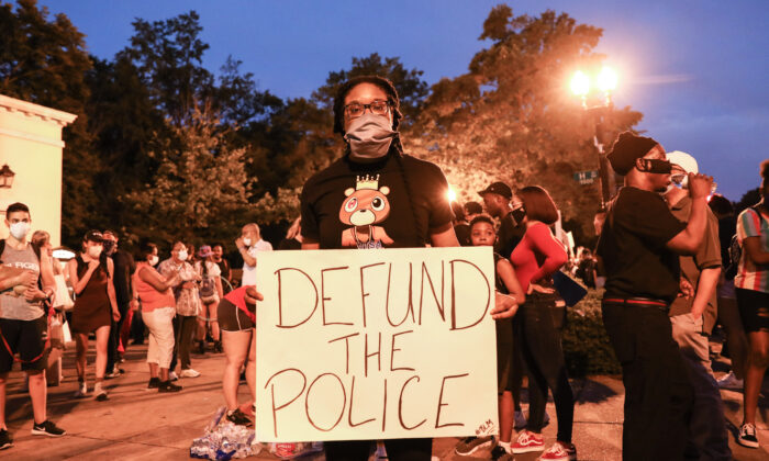 """A protester holds a """"Defund the Police"""" sign during a protest near the White House following the May 25 death of George Floyd in police custody, in Washington on June 6, 2020. (Charlotte Cuthbertson/The Epoch Times)"""