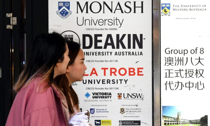 People walk past signage for Australian universities in Melbourne's central business district on June 10, 2020, (William West/AFP via Getty Images)