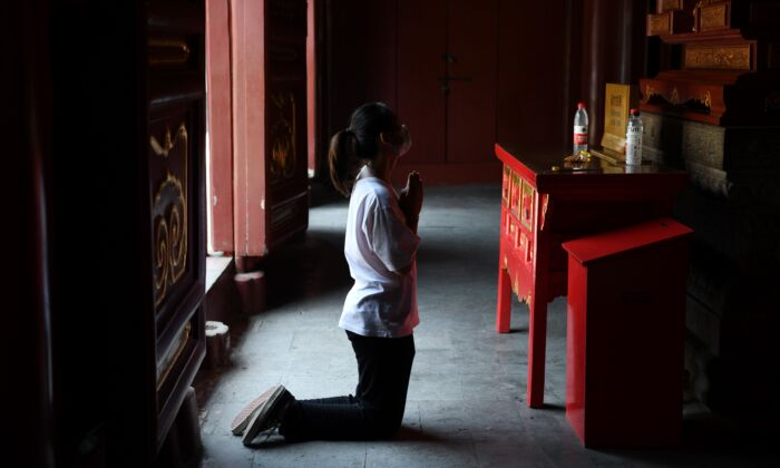 A woman wearing a mask prays at the Lama Temple in Beijing, China after it reopened on June 10, 2020. (GREG BAKER/AFP via Getty Images)