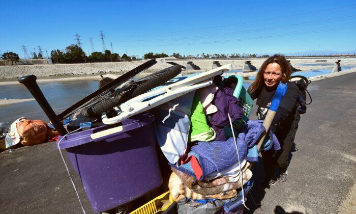 Melissa Lanning pulls her cart of belongings beside the Santa Ana River in Anaheim, Calif., on Feb. 20, 2018. (Frederic J. Brown/AFP via Getty Images)