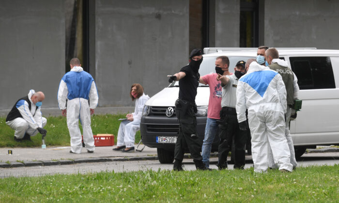 Police officers and forensic technicians wearing face masks work at the scene of a reported assault on staff at a school in Vrutky, Slovakia, on June 11, 2020. (Radovan Stoklasa/Reuters)