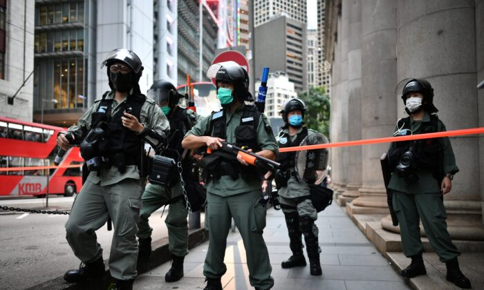Riot police officers stand guard ahead of a pro-democracy march in the Central district of Hong Kong on June 9, 2020, as the city marks the one-year anniversary since pro-democracy protests erupted following opposition to a bill allowing extraditions to mainland China. (Anthony Wallace/AFP via Getty Images)