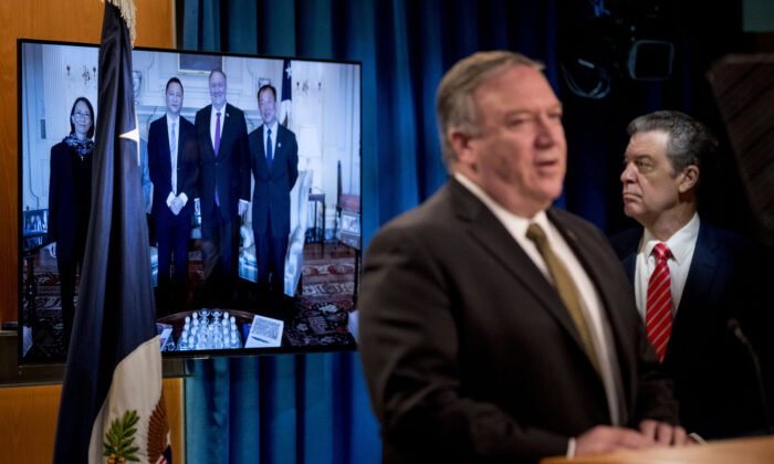 An image of survivors of the 1989 Tiananmen Square protests posing for a photograph with US Secretary of State Mike Pompeo is displayed as Pompeo, foreground, accompanied by Sam Brownback, Ambassador at Large for International Religious Freedom(R), speaks at a news conference at the State Department in Washington on June 10, 2020. (ANDREW HARNIK/POOL/AFP via Getty Images)