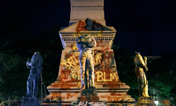 The statues on the Confederate monument are covered in graffiti and beheaded after a protest in Portsmouth, Va., on June 10, 2020. (Kristen Zeis/The Virginian-Pilot via AP)