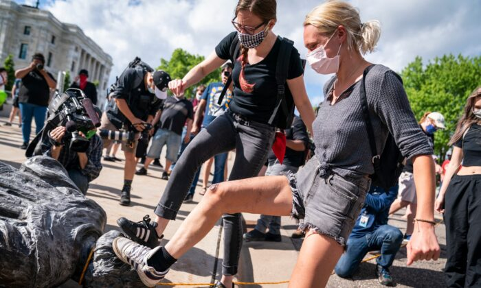 People take turns stomping the Christopher Columbus statue after it was toppled in front of the Minnesota State Capitol in St. Paul, Minn., on  June 10, 2020. (Leila Navidi/Star Tribune via AP)