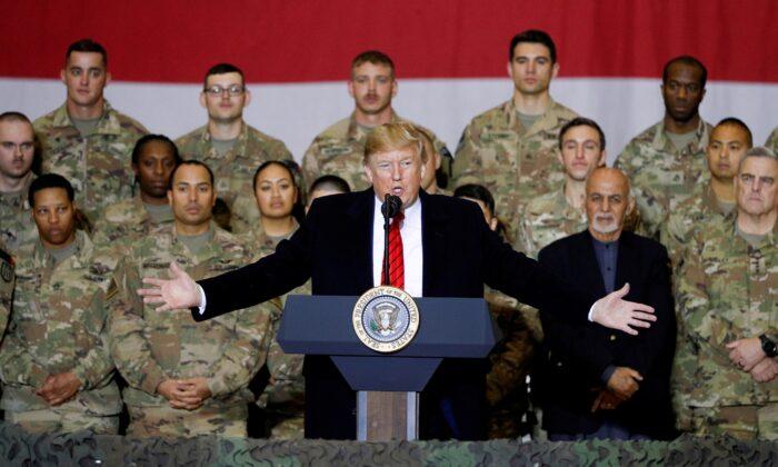 President Donald Trump delivers remarks to U.S. troops, with Afghanistan President Ashraf Ghani standing behind him, during an unannounced visit to Bagram Air Base, Afghanistan, on Nov. 28, 2019. (Tom Brenner/Reuters)
