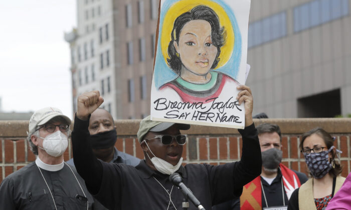 A man holds up a placard showing fallen Breonna Taylor, as he addresses a rally in Boston, Mass., on June 9, 2020. (Steven Senne/AP Photo)