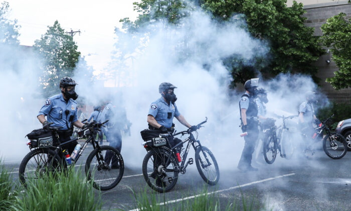Police officers deploy tear gas and pepper spray to corral protesters before detaining them during the sixth night of protests and violence following the death of George Floyd, in Minneapolis, Minn., on May 31, 2020. (Charlotte Cuthbertson/The Epoch Times)