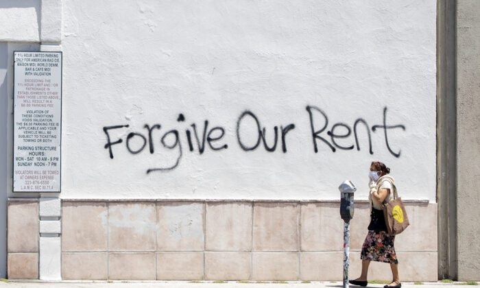 A woman wearing a mask walks past a wall bearing graffiti that asks for rent forgiveness amid the COVID-19 pandemic, in Los Angeles on May 1, 2020. (Valerie Macon/AFP via Getty Images)