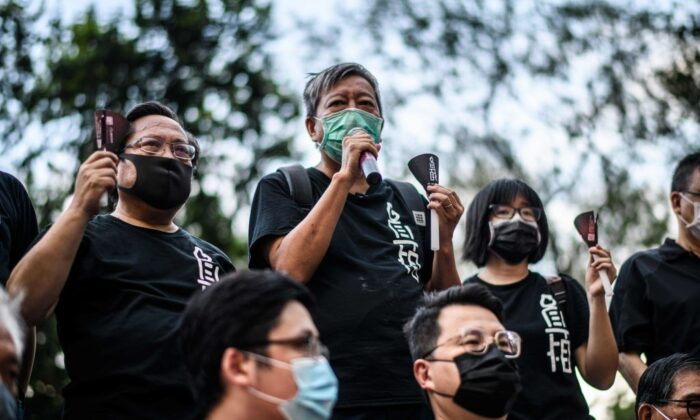 Albert Ho (top L) and  Lee Cheuk-yan (top C) of the Alliance in Support of Patriotic Democratic Movements of China, speak while holding candles before entering Victoria Park in Hong Kong on June 4, 2020. (Anthony Wallace/AFP via Getty Images)