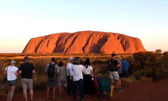 Tourists gather to watch sunset colours on Uluru, also known as Ayers rock, after a permanent ban on climbing the monolith at the Uluru-Kata Tjuta National Park in Australia's Northern Territory on October 26, 2019. (Saeed Khan/AFP via Getty Images)