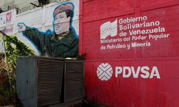 The logo of the Venezuelan state oil company PDVSA is seen next to a mural depicting Venezuela's late President Hugo Chavez at a gas station in Caracas, Venezuela, on March 2, 2017.  (Carlos Garcia Rawlins/Reuters)