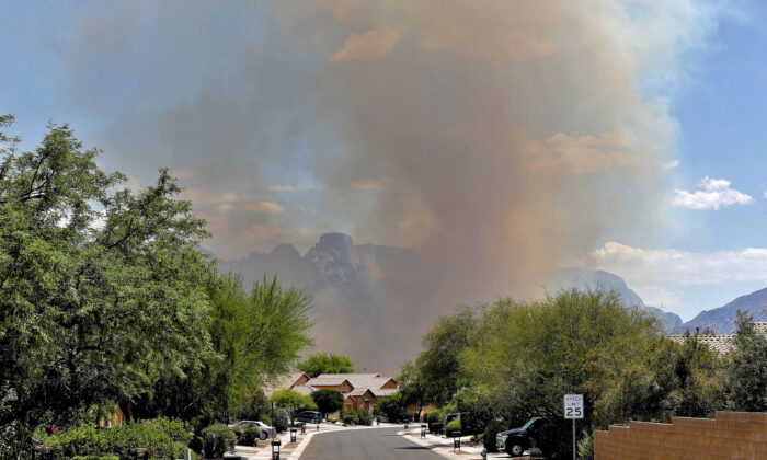 The Bighorn Fire backdrops a community along the western side of the Santa Catalina Mountains, in Tucson Ariz., on June 12, 2020. (Matt York/AP Photo)