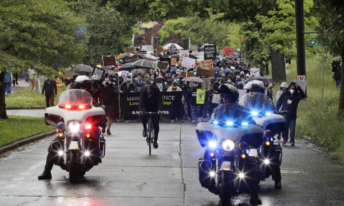 Police on motorcycles ride ahed of protesters organized by Black Lives Matter Seattle-King County, in Seattle, June 12, 2020. (AP Photo/Ted S. Warren)
