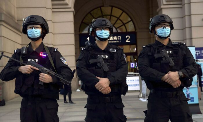 "Police officers stand guard outside Hankou Railway Station ahead of the resumption of train services in Wuhan on April 8, 2020. Holding Beijing to account for its coverup of the virus outbreak was one of the topics for discussion at a recent online forum titled ""China at a Crossroads: Standing Up for Human Rights During the Pandemic."" (AP Photo/Ng Han Guan)"