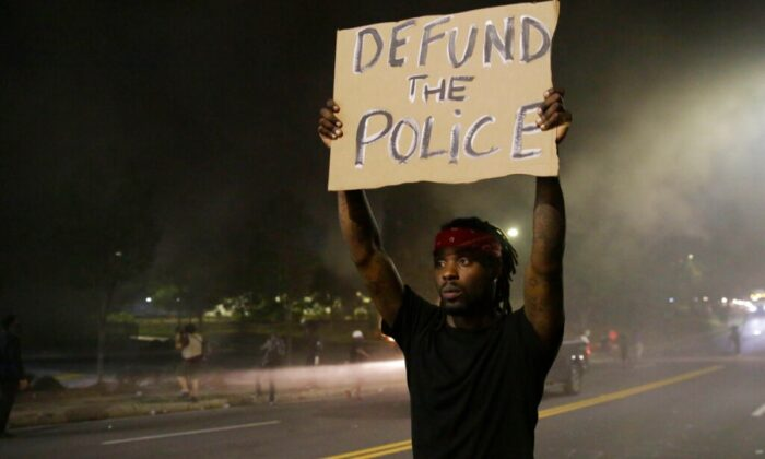 A man holds up a sign amid smoke of a fire during a protest in Atlanta, Ga., on June 13, 2020. (Brynn Anderson/AP Photo)
