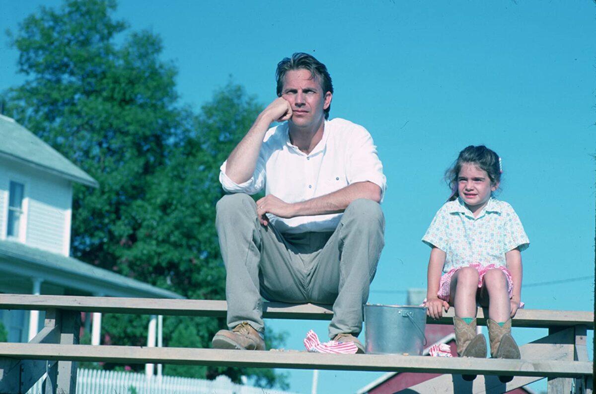 "man and girl sit on bleachers in ""Field of Dreams"""