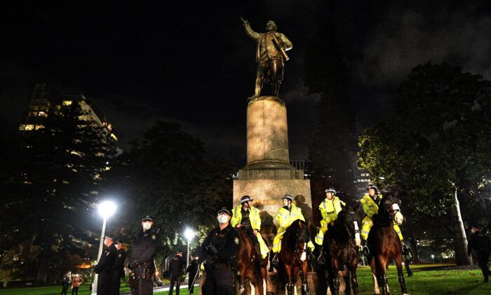 Police stand guard at the statue of Captain Cook in Hyde Park during a protest rally against Aboriginal deaths in custody and to show solidarity with Black Lives Matter movement, in Sydney on June 12, 2020. (Saeed Khan/AFP via Getty Images)
