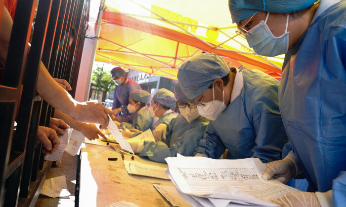 Medical workers sort nucleic acid test results for the citizens at a hospital in Beijing on June 14, 2020. (Lintao Zhang/Getty Images)