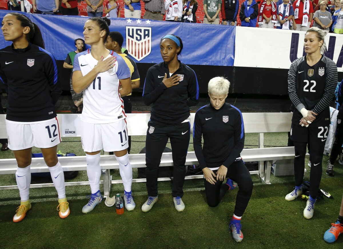 Megan Rapinoe (R) kneels