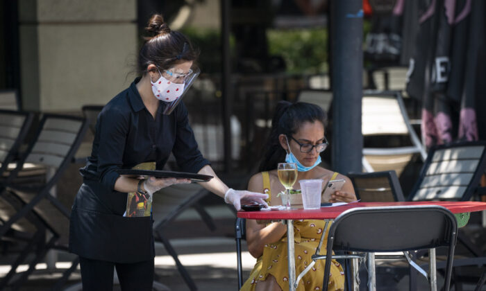 A waiter at Raku, an Asian restaurant in Bethesda, wears a protective face mask she serves customers outdoors amid the coronavirus pandemic in Bethesda, Maryland, on June 12, 2020. (Sarah Silbiger/Getty Images)