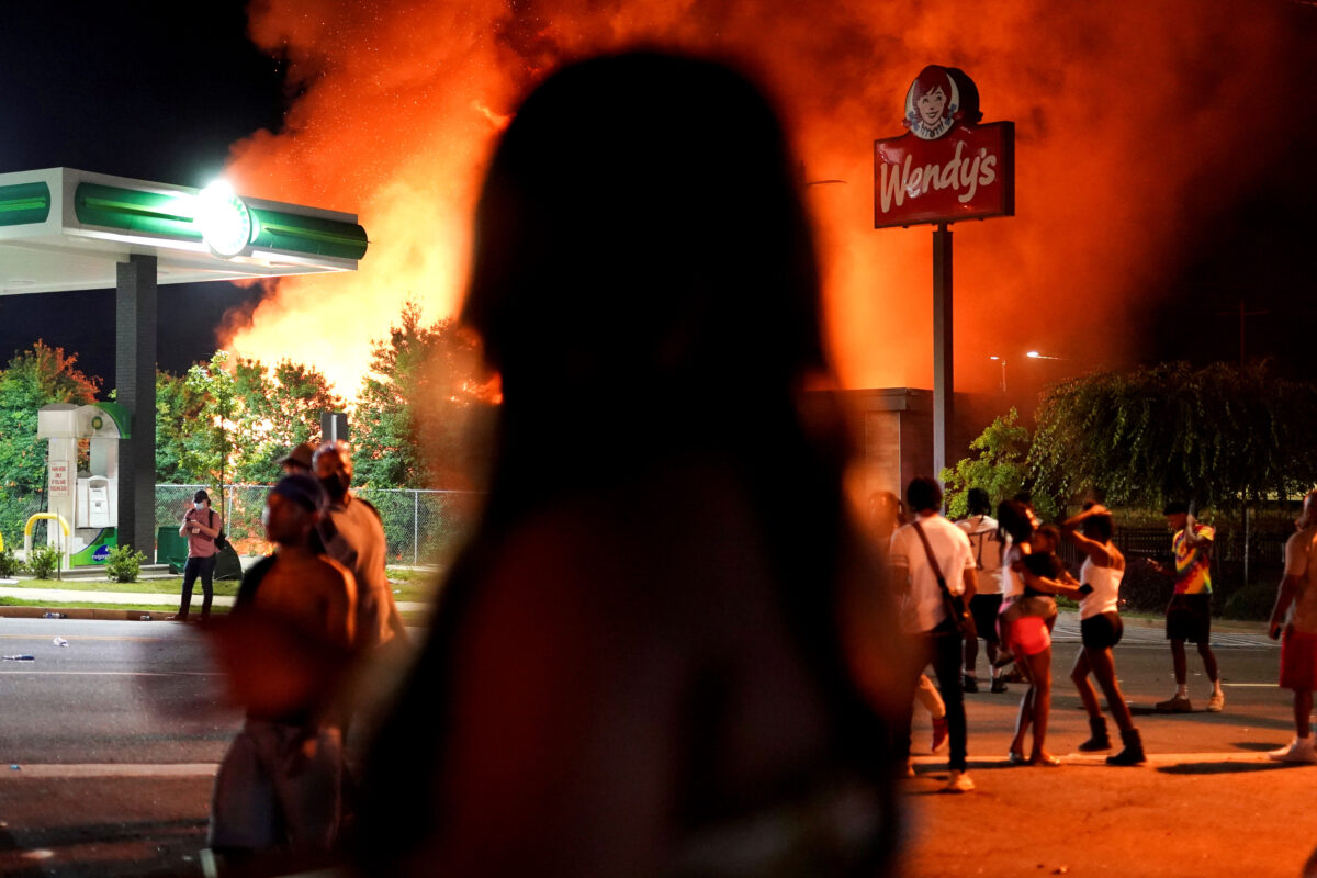 People watch as a Wendy's burns