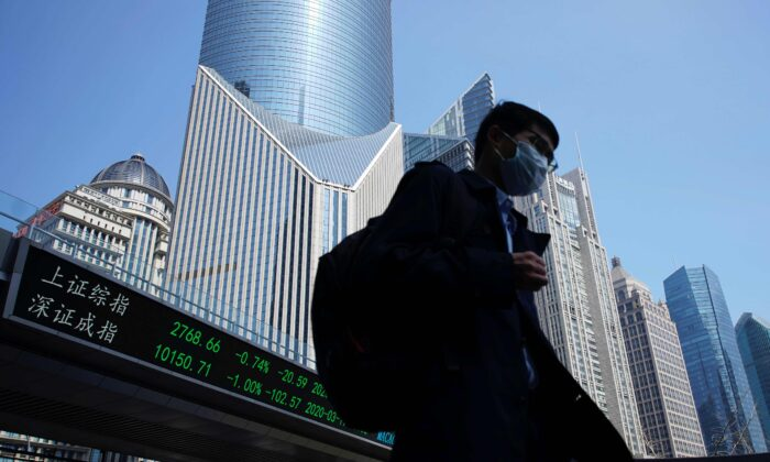 A pedestrian wearing a face mask walks near an overpass with an electronic board showing stock information, following an outbreak of the coronavirus disease (COVID-19), at Lujiazui financial district in Shanghai, China, on March 17, 2020. (Aly Song/Reuters)