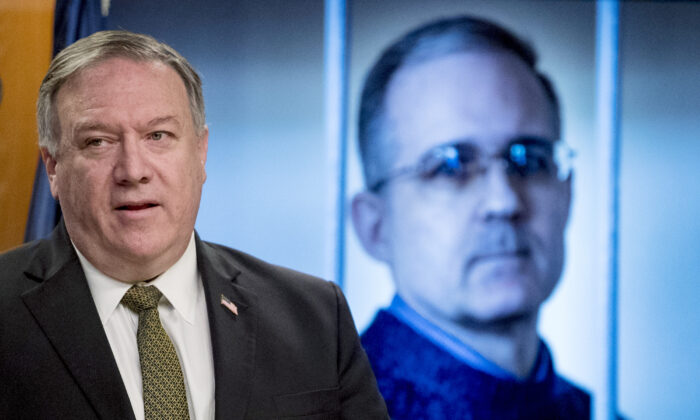 An image of Paul Whelan, a former U.S. Marine who was arrested for alleged spying in Moscow, is displayed behind Secretary of State Mike Pompeo, at a news conference at the State Department in Washington, on June 10, 2020. (AP Photo/Andrew Harnik, Pool)
