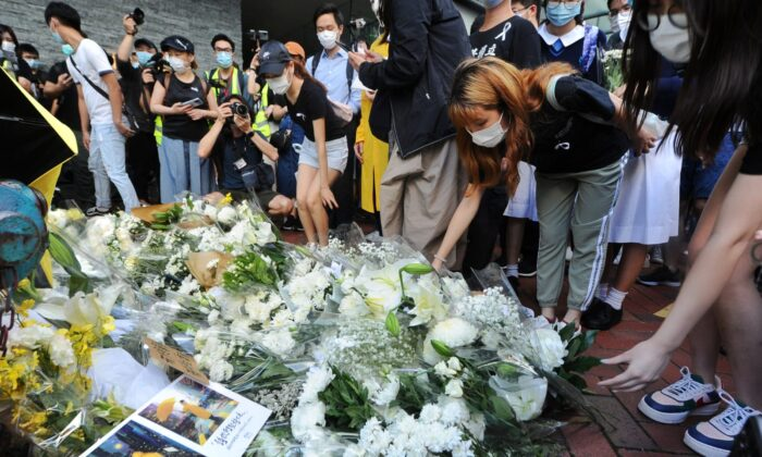 People lay down flowers to mourn the death of a local protester, near the Pacific Place mall in Admiralty, Hong Kong, on June 15. 2020. (Song Bilung/The Epoch Times)