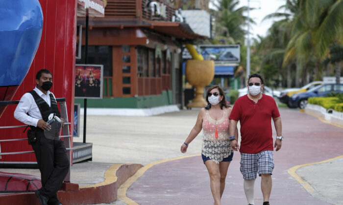 Tourists walk past restaurants and shops along an empty sidewalk in Cancun, Mexico on June 13, 2020. (Victor Ruiz/AP)