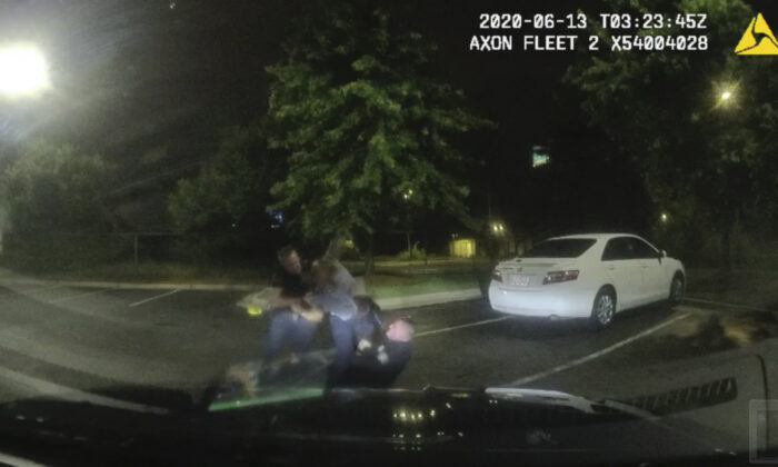 A dashboard camera shows Rayshard Brooks (C) struggling with officers Garrett Rolfe (L) and Devin Brosnan (R) in the parking lot of a Wendy's restaurant, in Atlanta, Ga., on June 13, 2020. (Atlanta Police Department via AP)
