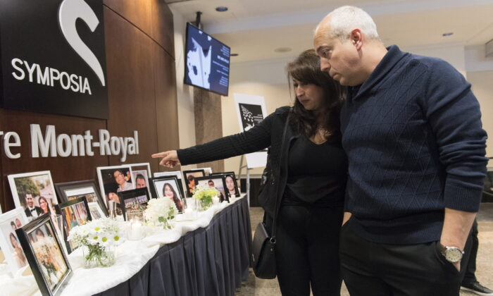 People pause at a memorial prior to a ceremony to remember those who lost their lives in Ukraine International Airlines Flight 752, in Montreal, Canada, on Jan. 19, 2020. (Graham Hughes/The Canadian Press)