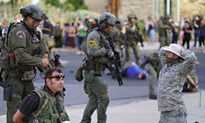 Albuquerque police detain members of the New Mexico Civil Guard, an armed civilian group, following the shooting of a man during a protest over a statue of Spanish conquerer Juan de Oñate in Albuquerque, N.M. on June 15, 2020. (Adolphe Pierre-Louis/The Albuquerque Journal via AP)