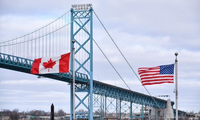 Canadian and American flags fly near the Ambassador Bridge at the Canada-USA border crossing in Windsor, Ont. in this file photo. (Rob Gurdebeke/The Canadian Press)