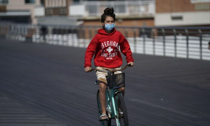 A young girl in a mask rides her bike  along the boardwalk in Long Beach, New York as people get started on the Memorial Day weekend on May 22, 2020. (Timothy A. Clary/AFP via Getty Images)