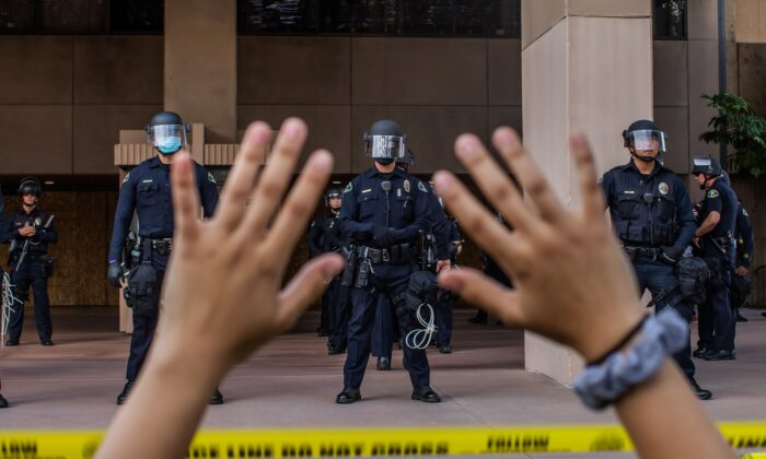 A demonstrator at a protest over the death of George Floyd holds her hands up while she kneels in front of the police at City Hall in Anaheim, Calif., on June 1, 2020. (Apu Gomes/AFP via Getty Images)
