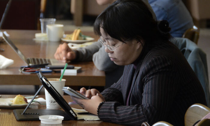 A woman reads her phone and tablet at a cafe in Beijing on Nov. 2, 2012. (WANG ZHAO/AFP via Getty Images)