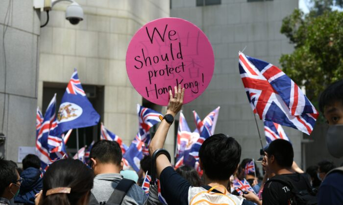 A group of people call on Britain to put pressure on Beijing during a protest outside the British consulate in Hong Kong on October 1, 2019. (Mohd Rasfan/RASFAN/AFP/Getty Images)