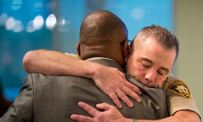 Jon Ponder, founder of HOPE for Prisoners, embraces a Las Vegas police officer. (Courtesy of Jon Ponder)