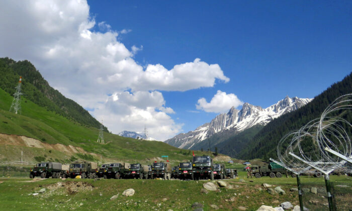 Indian army soldiers walk past their parked trucks at a makeshift transit camp before heading to Ladakh, near Baltal, southeast of Srinagar, on June 16, 2020. (Stringer/Reuters)