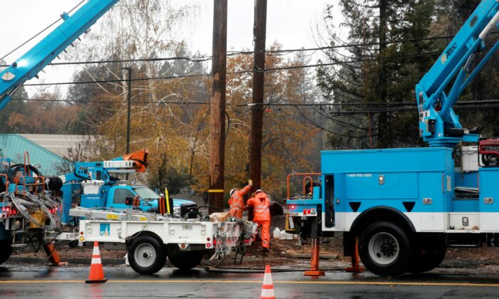 PG&E works on power lines to repair damage caused by the Camp Fire in Paradise, Calif., on Nov. 21, 2018. (Elijah Nouvelage/Reuters)