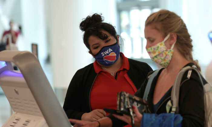 A Southwest Airlines employee wears a protective mask while assisting a passenger at Los Angeles International Airport (LAX) during the COVID-19 outbreak in Los Angeles, Calif., on May 23, 2020. (Patrick T. Fallon/Reuters)