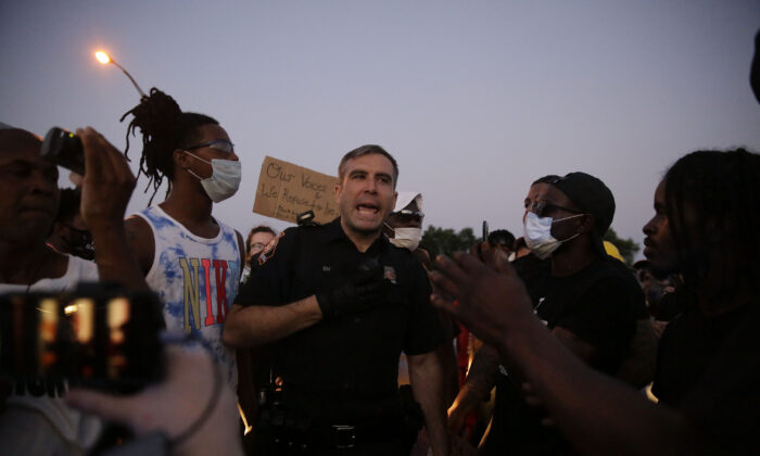 An Atlanta police officer talks with protesters near the Wendy's where Rayshard Brooks was shot and killed by police the day prior in the restaurant's drive-through line in Atlanta, Ga., on June 13, 2020. (Brynn Anderson/AP Photo)