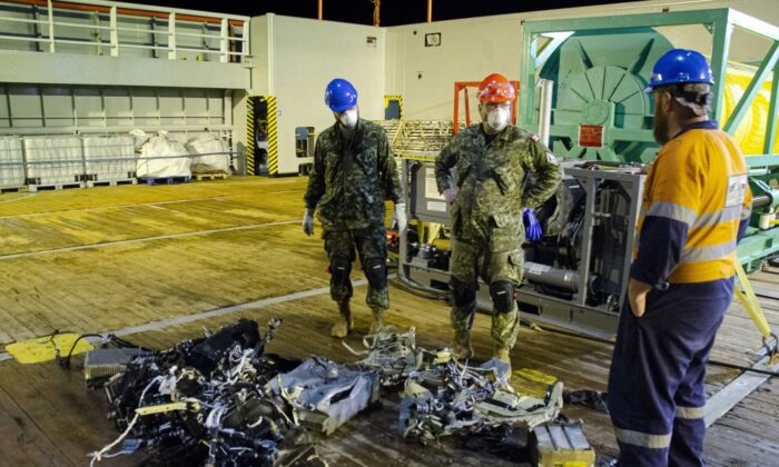 CF members and EDT Hercules personnel inspect recovered parts of the helicopter Stalker 22 during recovery operations for the aircraft in the Mediterranean Sea on May 31, 2020.  (Cdr Robert Watt/THE CANADIAN PRESS/HO-Department of National Defence)