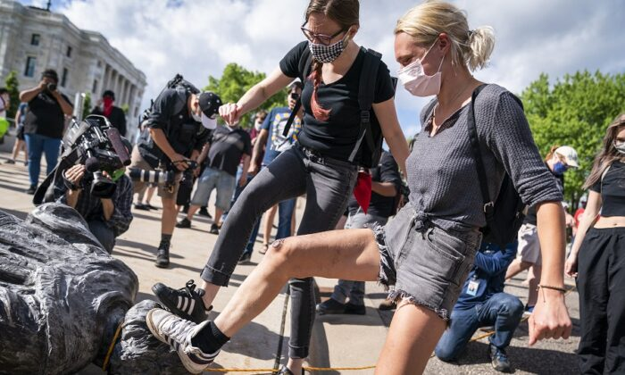 People take turns stomping a statue of Christopher Columbus after it was toppled in front of the Minnesota State Capitol in St. Paul, Minn., on June 10, 2020. (Leila Navidi/Star Tribune via AP)