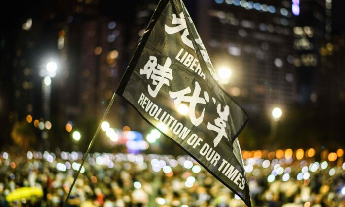 Attendees raise a flag that reads 'Liberate Hong Kong, Revolution of Our Times' during a candlelit remembrance in Victoria Park in Hong Kong on June 4, 2020. (ANTHONY WALLACE/AFP via Getty Images)