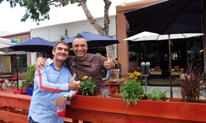 Happy restaurant owners Laurent Vrignaud (L) and Alessandor Pirozzi celebrate the opening of the promenade in Laguna Beach, Calif., on June 15, 2020. (Jamie Joseph/The Epoch Times)